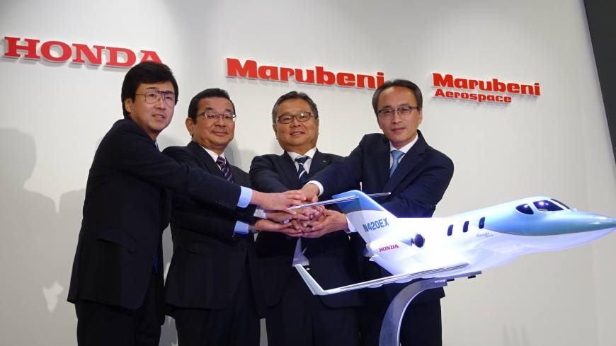 Executives from Honda and trading house Marubeni Corp. join hands at a news conference Wednesday in Tokyo.   SHUSUKE MURAI