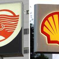 Signs of gas stands operated by Idemitsu Kosan Co. (left) and Showa Shell Sekiyu K.K. are seen in this combo photo. | KYODO