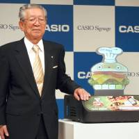 Kazuo Kashio, then-president of Casio Computer Co., attends a news conference in November 2012 in Tokyo to unveil a small projector with a built-in screen in the shape of a person or character. | KYODO