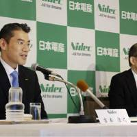 New Nidec Corp. President Hiroyuki Yoshimoto (left) speaks during a news conference next to Chairman Shigenobu Nagamori in Kyoto on Wednesday. | KYODO