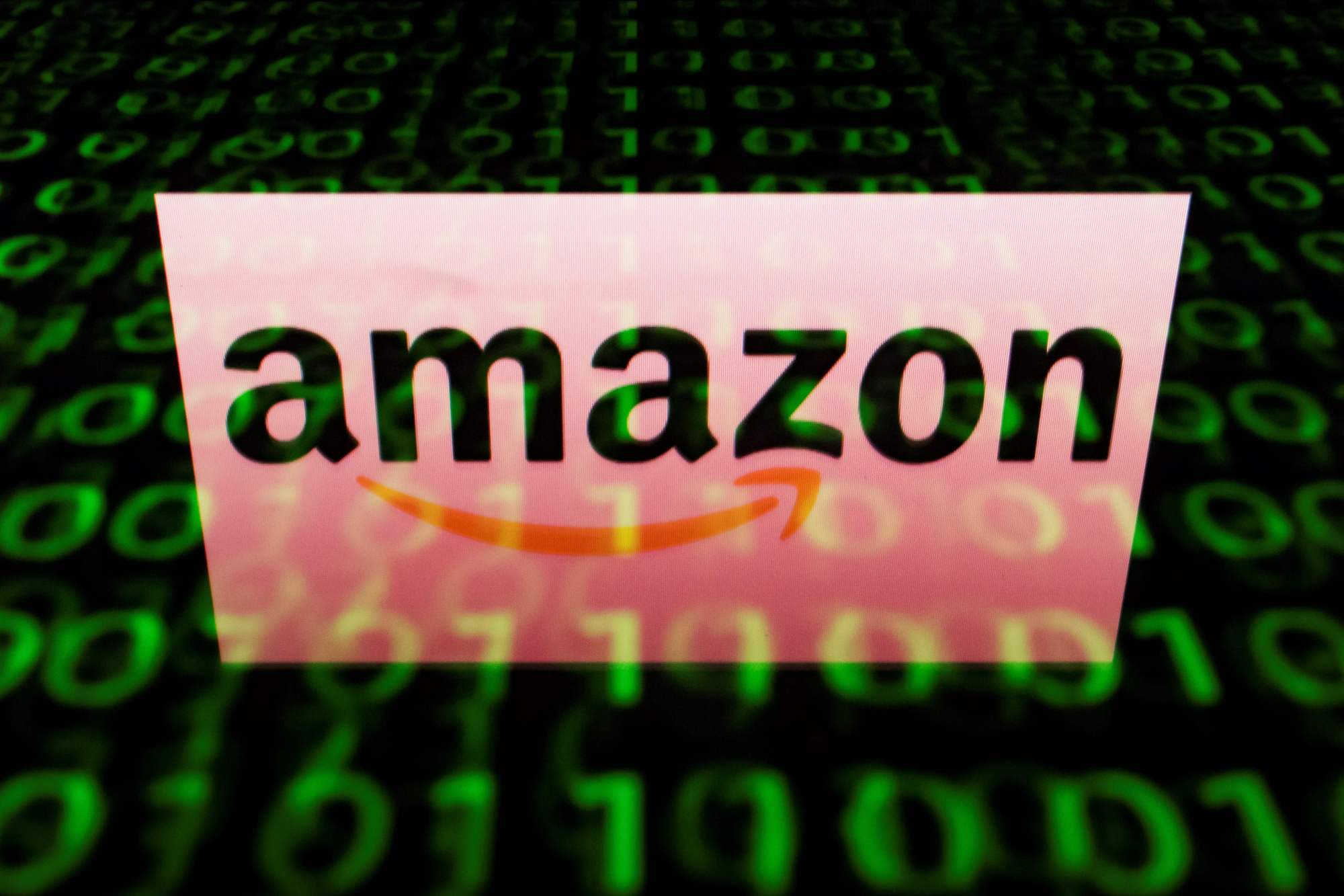 The Amazon logo is displayed on a screen and reflected on a tablet in Paris in April. Amazon set its sights on the pharmacy market Thursday with the acquisition of tech-focused retailer PillPack, sending shock waves throug.h the sector over prospects of disruption by the U.S online colossus. | AFP-JIJI