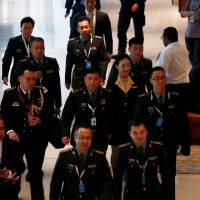 People's Liberation Army's Lt. Gen. He Lei (center) arrives at the IISS Shangri-la Dialogue in Singapore Friday. | REUTERS