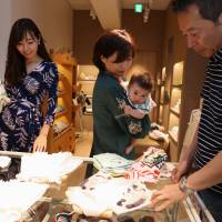 A couple shop with their daughter-in-law (left) and grandchild at a Sayegusa Inc. clothing store in Tokyo's Ginza district. The nation's savings-rich elderly spend about ¥9.7 trillion a year on their offspring. | BLOOMBERG