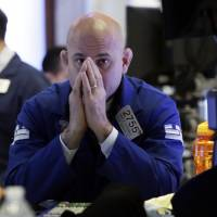 Specialist Mark Fitzgerald works on the floor of the New York Stock Exchange Tuesday. U.S. stock markets opened sharply lower Tuesday as tensions over trade between the U.S. and China seem closer to a boil. | AP