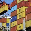 A container is loaded onto a cargo ship at a port in Qingdao in east China's Shandong province in April. China accused the United States on Thursday of using pressure tactics and blackmail in threatening to impose tariffs on hundreds of billions of dollars of Chinese imports.