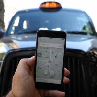 A photo illustration shows the Uber app and a black cab in London Tuesday. | REUTERS