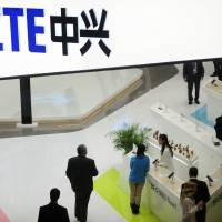 People gather at the ZTE booth at the Mobile World Congress, the world's largest mobile phone trade show, in Barcelona, Spain, in 2014. Shares in ZTE Corp. have fallen 42 percent in Hong Kong after the Chinese telecoms equipment maker agreed to pay a $1 billion penalty to the U.S. government and replace its top managers. | AP