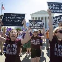 Pro-life and anti-abortion advocates demonstrate in front of the Supreme Court early Monday. | AP