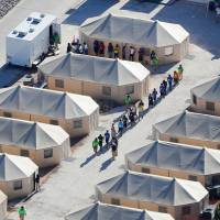 Immigrant children now housed in a tent encampment under the new 'zero tolerance' policy by the Trump administration are shown walking in single file at the facility near the Mexican border in Tornillo, Texas, June 19. | REUTERS