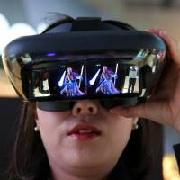 A woman plays the game 'Star Wars: Jedi Challenges' with a Lenovo augmented-reality headset at the Mobile World Congress in Barcelona, Spain, on Feb. 27. | BLOOMBERG