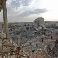 Syrians gather amid destruction in Zardana, in the mostly rebel-held northern Syrian Idlib province, in the aftermath of following airstrikes in the area late on Friday. Ai strikes in northwestern Syria, thought to have been carried out by regime ally Russia killed 38 civilians including four children, a Britain-based monitor said. | AFP-JIJI