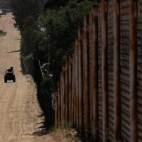 Border patrol agents use all-terrain vehicles while searching for illegal immigrants along the wall on the U.S. border with Mexico in Tecate, California, on Monday. | REUTERS