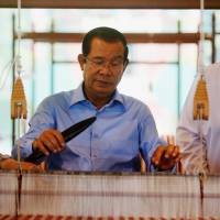 Cambodian Prime Minister Hun Sen weaves a krama cotton scarf during an attempt to break the world record for weaving the longest cotton scarf in Phnom Penh on June 7. | REUTERS