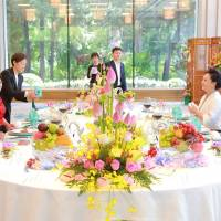 Chinese President Xi Jinping and his wife, Peng Liyuan, chat with North Korean leader Kim Jong Un and his wife, Ri Sol Ju, during a luncheon at the Diaoyutai State Guesthouse in Beijing on Wednesday.   AFP-JIJI