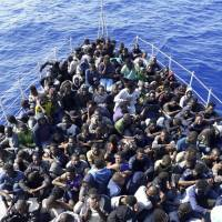 African migrants to Europe who were rescued from boats in distress in the Mediterranean on their way to Europe are brought to shore near Tripoli on Sunday. | AP