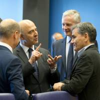 Greek Finance Minister Euclid Tsakalotos (right) speaks with European Commissioner for Economic and Financial Affairs Pierre Moscovici (second from left) during a meeting of eurogroup finance ministers at EU headquarters in Luxembourg on Thursday. | AP