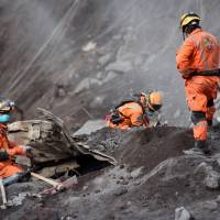 Volunteer firefighters search for victims of Sunday's Fuego Volcano eruption in Alotenango, a municipality in Sacatepequez Department, southwest of Guatemala City, on Wednesday. New explosions boomed from Guatemala's fearsome Fuego volcano on Wednesday, unleashing fresh torrents of molten mud and ash down slopes where officials said 75 people had been killed and 200 were still missing.   AFP-JIJI