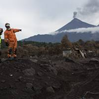 A rescue worker indicates to a bulldozer operator where to dig at a home during the search for the remains of 40 relatives who were killed by the eruption of the Volcan de Fuego, or Volcano of Fire, in San Miguel Los Lotes, Guatemala, Wednesday. | AP