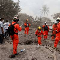 Mexican rescue workers search for the family of Eufemia Garcia, 48, who lost 50 members of her family during the eruption of the Fuego volcano, in San Miguel Los Lotes, Escuintla, Saturday. | REUTERS