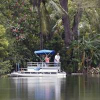 A couple watch from a pontoon boat at Silver Lakes Rotary Nature Park in Davie, Florida, on Friday as authorities worked to capture an apparent killer alligator in a nearby pond. | AP