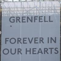 Banners of support are unveiled on the outside of Grenfell Tower in west London on June 6. | AP