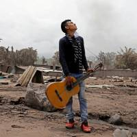 Brian Rivera, who lost 13 members of his family during the eruption of the Fuego volcano, holds his sister's guitar near debris of his home at San Miguel Los Lotes, Escuintla, Guatemala, Thursday. | REUTERS