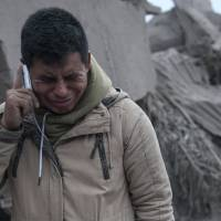 Boris Rodriguez, 24, who is searching for his wife, cries after seeing the condition of his neighborhood, destroyed by the erupting Volcan de Fuego, or 'Volcano of Fire,' in Escuintla, Guatemala, Monday. The volcano exploded Sunday, sending ash high into the sky and lava flows cascading into rural hamlets on the mountain's slopes. | AP