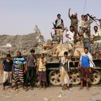 Tribal fighters loyal to the Yemeni government stand by a tank in the al-Faza area near Hodeida, Yemen, on June 1. | REUTERS