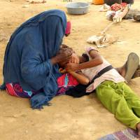 A displaced Yemeni woman from Hodeida comforts a child in their shelter at a make-shift camp for displaced people in the northern district of Yemen's Hajjah province onTuesday. Fierce fighting in the Hodeida area has already driven 5,200 families from their homes as pro-government forces advanced up the Red Sea coast, according to the U.N. | AFP-JIJI