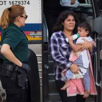 A woman carries a baby as she and other immigrants are dropped off at a bus station shortly after being released from detention through the 'catch and release' immigration policy on June 17 in McAllen, Texas. | AFP-JIJI