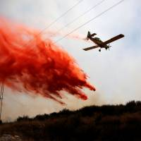 A firefighting aircraft flies over fields near the Israeli side of the border between Israel and the Gaza Strip, near kibbutz Or HaNer Sunday. | REUTERS