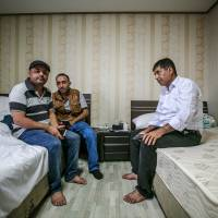 Omar Hassan (left) and Abdo Ahmed (center) sit with another Yemeni asylum-seeker in a hotel room in Jeju, South Korea, on Thursday.   BLOOMBERG