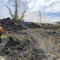 A Hawaiian Volcano Observatory geologist documents the Fissure 8 flow southeast of Four Corners, the intersection of Highways 132 and 137, near Pahoa, Hawaii, Saturday. | U.S. GEOLOGICAL SURVEY / VIA AP
