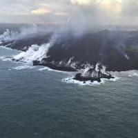 An aerial view is seen Saturday of the Kapoho ocean entry, showing the extent of the lava delta, now about 200 acres in size, that has formed over the past six days as it enters the Pacific Ocean as Kilauea Volcano continues its eruption cycle near Pahoa on the island of Hawaii. Across the front of the delta, plumes of laze, created by molten lava interacting with seawater, appeared diminished early morning, but was probably due to a change in atmospheric conditions rather than a change in the amount of fissure 8 lava reaching the ocean. | U.S. GEOLOGICAL SURVEY / VIA AP