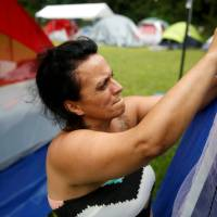 Tina Yoon, 43, who was forced by volcanic activity to leave her home in Leilani Estates, adjusts her tent at an evacuation center in Keaau on the island of Hawaii on Sunday. | REUTERS