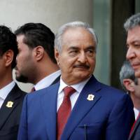 Khalifa Hifter (center), the military commander who dominates eastern Libya, leaves after an international conference on Libya in Paris May 29. | REUTERS