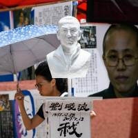 A bust of late Chinese Nobel laureate Liu Xiaobo and a poster of his wife, Liu Xia, are displayed outside a shopping mall in Hong Kong on Friday, ahead of Monday's annual candlelight vigil. This year's event will mark the 29th anniversary of the 1989 Tiananmen Square massacre. | AFP-JIJI