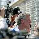 New York City Mayor Bill de Blasio looks through a closed gate at the Port of Entry facility, Thursday in Fabens, Texas, where tent shelters are being used to house separated family members. Mayors from more than a dozen U.S. cities, including New York and Los Angeles, gathered near the holding facility for immigrant children on the Texas border with Mexico to call for the immediate reunification of immigrant children with their families.