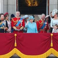 Royal family members (from left) Meghan, Duchess of Sussex; Prince Charles; Catherine, Duchess of Cambridge (with Princess Charlotte and Prince George); and Prince William, Duke of Cambridge, stand on the balcony of Buckingham Palace to watch a fly-past of aircraft by the Royal Air Force in London on Saturday during the Trooping the Colour ceremony to mark the official birthday of the queen, whose actual birthday is on April 21. | AFP-JIJI