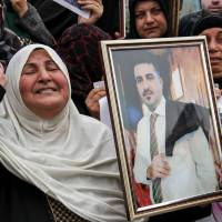 An Iraqi woman holds up a portrait of a missing relative — who was held captive by Islamic State fighters — during a demonstration in the northern city of Mosul on April 13. | AFP-JIJI