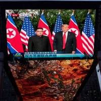 A giant TV screen in Beijing shows U.S. President Donald Trump and North Korean leader Kim Jong Un shake hands Tuesday following a signing ceremony at the end of their historic summit in Singapore.   AFP-JIJI
