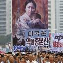 Tens of thousands of men and women pump their fists in the air and chant as they carry placards with anti-American propaganda slogans at Pyongyang's central Kim Il Sung Square on June 25, 2017.