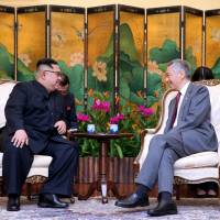 North Korean leader Kim Jong Un sits with Singaporean Prime Minister Lee Hsien Loong at the Istana in the city-state Sunday. | REUTERS