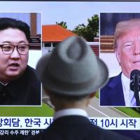 A man watches a TV screen showing file footage of U.S. President Donald Trump and North Korean leader Kim Jong Un during a news program at the main railway station in Seoul on Monday, a day ahead of the two leader's historic summit in Singapore.   AP