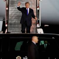 U.S. President Donald Trump waves as he steps off his plane upon arriving at Paya Lebar Air Base in Singapore on Sunday, ahead of a summit with North Korean leader Kim Jong Un. | REUTERS