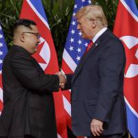 U.S. President Donald Trump shakes hands with North Korea leader Kim Jong Un at the Capella resort in Singapore on Tuesday. | AP