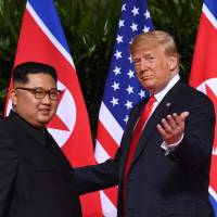 US President Donald Trump gestures as he meets with North Korea's leader Kim Jong Un at the start of their historic U.S.-North Korea summit, at the Capella Hotel on Sentosa island in Singapore on Tuesday. | AFP-JIJI