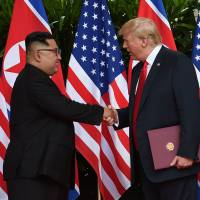 U.S. President Donald Trump and North Korea's leader Kim Jong Un shake hands during the signing of a document after their summit at the Capella Hotel on Sentosa island in Singapore on Tuesday. | REUTERS