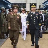 South Korean Maj. Gen. Kim Do-gyun (right) is escorted by a North Korean officer after crossing to North Korea for the meeting at the northern side of Panmunjom in the Demilitarized Zone on Friday.   SOUTH KOREA DEFENSE MINISTRY / VIA AP