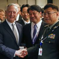 U.S. Defense Secretary Jim Mattis (left), Japanese Defense Minister Itsunori Onodera and Chinese People's Liberation Army's Academy of Military Science Deputy President He Lei pose for photos at a ministerial roundtable on the sidelines of the International Institute for Strategic Studies' Shangri-La Dialogue forum in Singapore on Saturday. | AP
